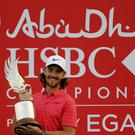 England's Tommy Fleetwood holds the trophy after he won the Abu Dhabi Championship