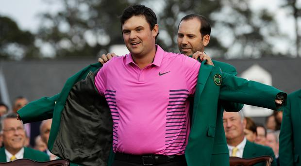 Patrick Reed is presented with his green jacket by Sergio Garcia