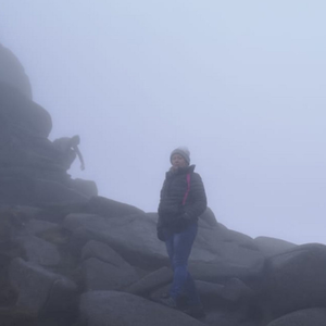 Lizann Hughes on Slieve Binnian with a ghostly figure in the background on the rocks behind her