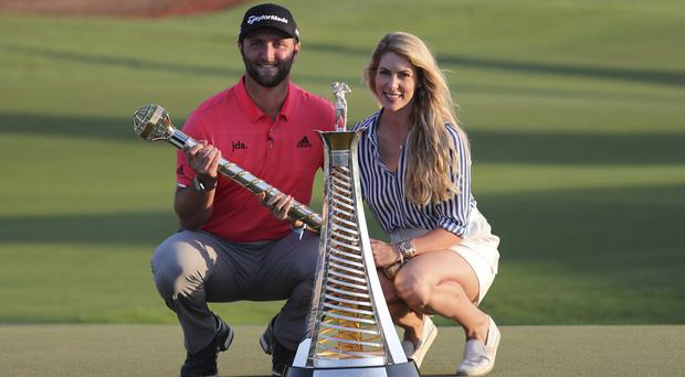 Jon Rahm (left) poses next to his fiancee Kelley after winning the DP World Tour Championship and Race to Dubai (Kamran Jebreili/AP)