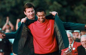 Tiger king: Tiger Woods is fitted with his 1997 Masters green jacket by the previous year's winner Nick Faldo