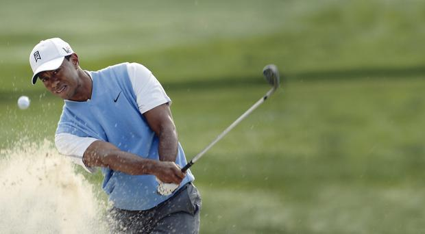 Tiger Woods of the United States plays a shot from a bunker during a practice round prior to the start of the 95th PGA Championship at Oak Hill Country Club on August 6, 2013