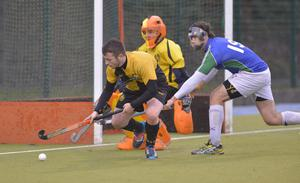 Out of reach: Andy Christie of Portrush shields the ball from Queen's ace Simon MacLeod
