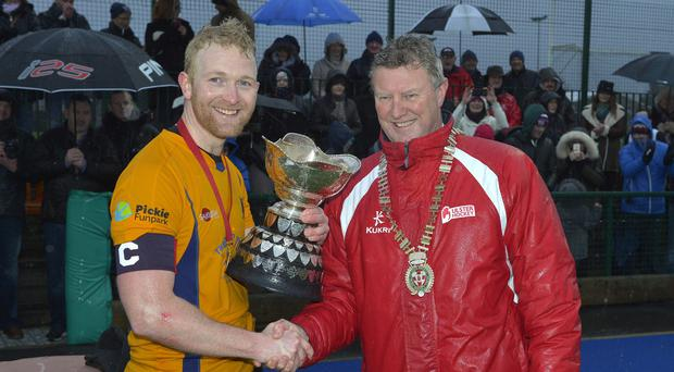 Mandatory Credit: Rowland White/PressEye Men's Hockey: Linden Cup Final Teams: Bangor (yellow) v Campbellians (black) Venue: Deramore Park Date: 1st January 2016 Caption: UHU President Davy Larmour presents the Linden Cup to Bangor Captain, James Trimble