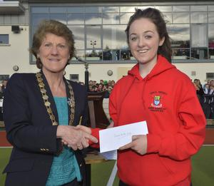 Consolation prize: Banbridge Academy's Katie McKee receives her Player of the Match award from Ulster Hockey president Ann Rosa at Lisnagarvey yesterday