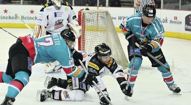 Sheffield's Danny Myers tries to keep the puck away from Belfast Giants players Kevin Saurette and Dustin Whitecotton