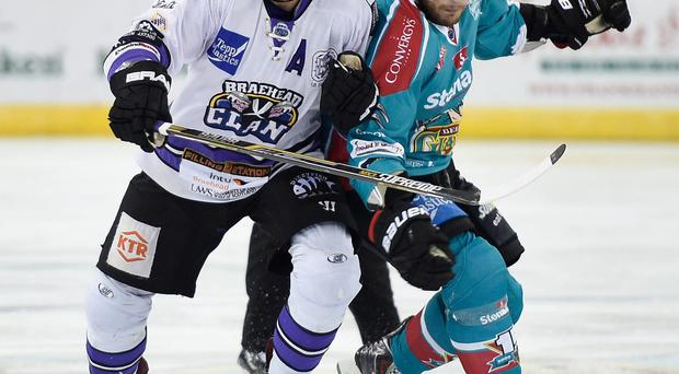 On the chase: Braehead Clan's Scott Aarssen fights for the puck with Belfast Giants captain Adam Keefe during Saturday night's game at the Odyssey Arena