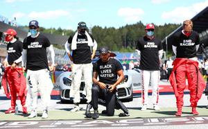 Divided: Lewis Hamilton 'takes a knee' before the Austrian Grand Prix yesterday but other drivers remaining standing