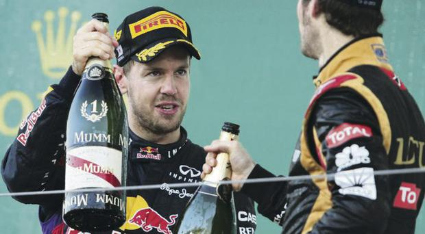 Number one: Sebastian Vettel toasts his victory at the Japanese Grand Prix yesterday as Romain Grosjean of Lotus looks on