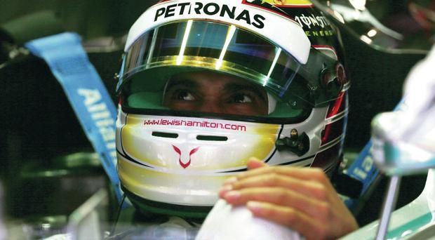 Ready to go: Lewis Hamilton of Mercedes GP sits in his car in the garage during practice ahead of the Spanish F1 Grand Prix