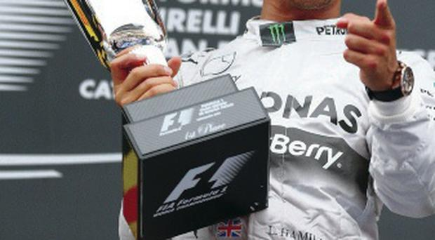 Champion: Lewis Hamilton celebrates his win in Spain