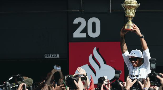 Golden boy: Mercedes' Lewis Hamilton celebrates with the BRDC trophy after winning the 2014 British Grand Prix at Silverstone
