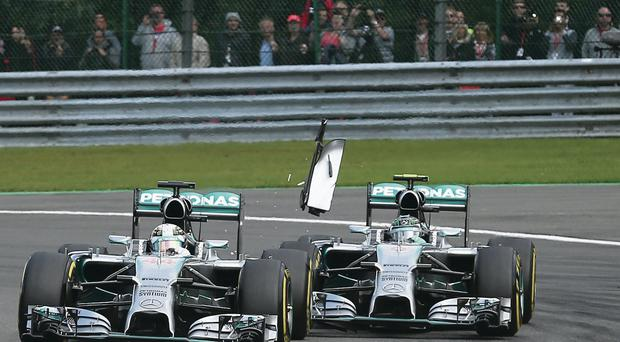 Collision course: Debris flies in the air as Nico Rosberg and Lewis Hamilton clash during the Belgian Grand Prix