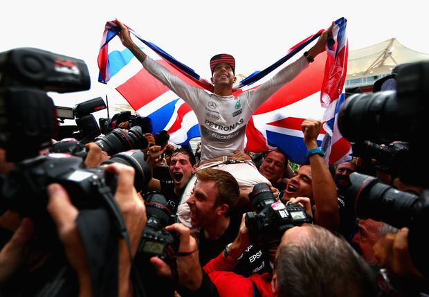 Flying the flag: Lewis Hamilton celebrates becoming a triple World champion after victory in the US Grand Prix