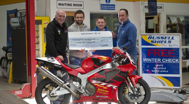 Cheque mate: Noel Johnston, Clerk of the Course at the UGP, with William Dunlop, Joey's son Gary Dunlop and Russell Shiels