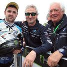 Michael Dunlop (Tyco BMW) celebrates winning the Superbike TT on the Isle of Man today with Tyco bosses Philip and Hector Neill.