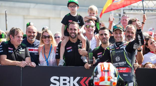 We are family: Jonathan Rea celebrates his Superpole win yesterday with wife Tatia, sons Jake and Tyler and members of his Kawasaki team