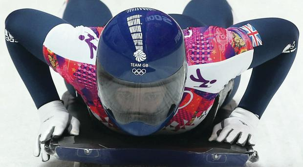Flying the flag: Lizzy Yarnold speeds down the track at the appropriately named Sanki Sliding Center on her way to Winter Olympic gold, sparking celebrations on the podium ahead of today's medal ceremony