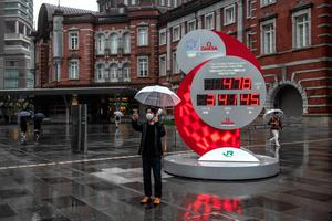 Waiting games: A man wearing a face mask takes a selfie next to a Tokyo 2020 Olympics countdown clock that has been adjusted for the new start date of July 23, 2021