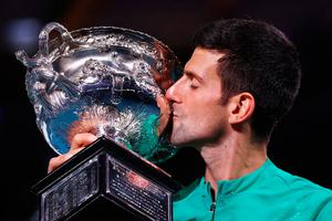 Taste of success: Novak Djokovic with his 18th Grand Slam trophy after winning the Australian Open for a ninth time