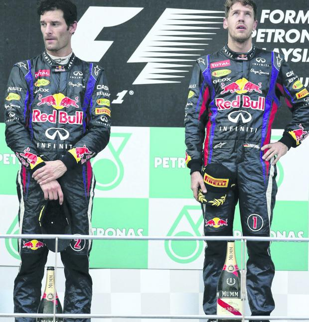 Red Bull driver Sebastian Vettel of Germany, right, and his teammate Mark Webber of Australia stand on the podium during the awarding ceremony for the Malaysian Formula One Grand Prix at Sepang, Malaysia, Sunday, March 24, 2013. Vettel won the race and Webber finished second. (AP Photo/Andy Wong)