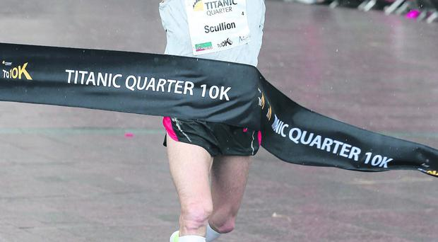 Stephen Scullion crosses the line to win the Titanic 10k Road Race in Belfast