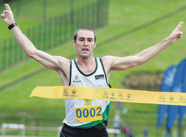 Emphatic victory: Home favourite Stephen Scullion crosses the finishing tape at the Mary Peters Track to win the Belfast Deep RiverRock Half Marathon