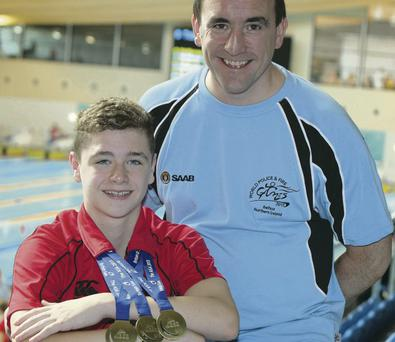 Top marks: Conor Ferguson shows off his three British Age Group gold medals alongside proud dad Peter