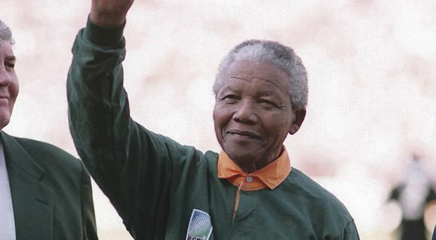 Nelson Mandela waves to crowds after his country wins the rugby world cup