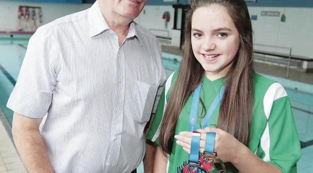 Golden girl: Ards' swimmer Rebecca Reid shows off the medals she won in Canada during the summer to coach Nelson Lindsay