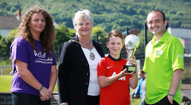 World in motion: Fionnuala Carolan from Active Communities Network, Deputy Lord Mayor of Belfast Maire Hendron and Scott Gillespie, Community Life Champion at Asda Shore Road, with Aaron Cush (12) from Springhill who took part in the Asda Foundation Mini World Cup