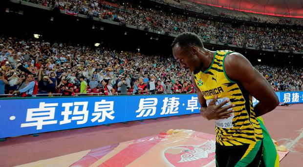 Take a bow: Usain Bolt salutes the Beijing crowd after taking 200m gold to go with the 100m title he won four days ago