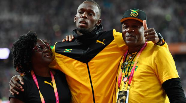 Emotional moment: Usain Bolt is embraced by his parents after failing to strike gold before beginning his retirement