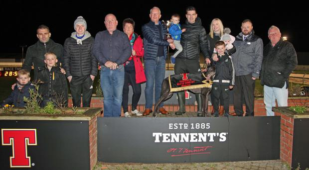 Family Gold: Ross Heggarty, Regional Sales Manager, Tennents NI presents the Tennents Gold Cup trophy to winning owner Shea Campbell, with his champion dog Stefan's Wee Bro, named after Shea's sons. Also on the podium are trainer Aidan McVeigh, Drumbo Racing Manager John Connor and Campbell family connections