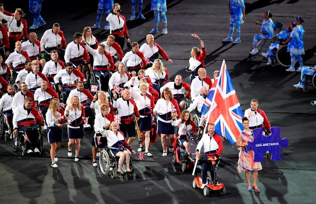 Centre stage: The Great Britain team are led out by flag bearer Lee Pearson during last night's opening ceremony