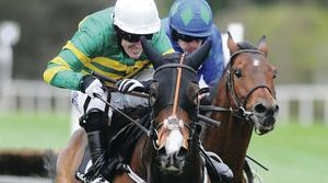 Tony McCoy powers Jezki to success in the Champion Hurdle at Punchestown yesterday with Ulster-owned Hurricane Fly in hot pursuit