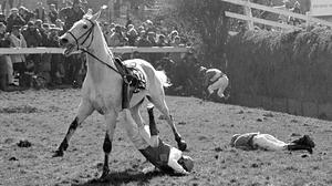 Jockey Tom Taaffe is dragged by his mount Sergeant Sprite after failing to clear the Beechers Brook jump in the Seagram Grand National at Aintree.