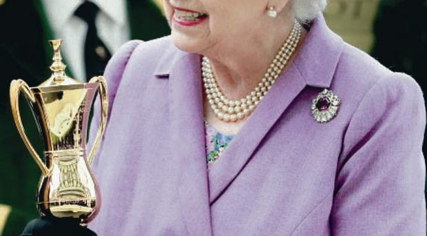 ASCOT, ENGLAND - JUNE 20: Queen Elizabeth II holds the Gold Cup after Ryan Moore riding Estimate won The Gold Cup during Ladies' Day on day three of Royal Ascot at Ascot Racecourse on June 20, 2013 in Ascot, England. (Photo by Chris Jackson/Getty Images for Ascot Racecourse)