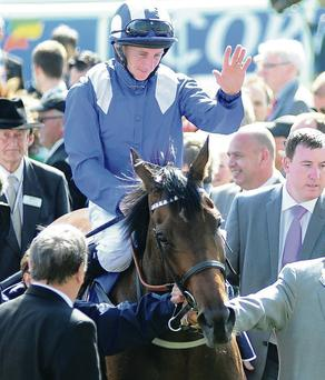 Wave of emotion: Paul Hanagan salutes the crowd after victory on Taghrooda in the Investec Oaks at Epsom yesterday
