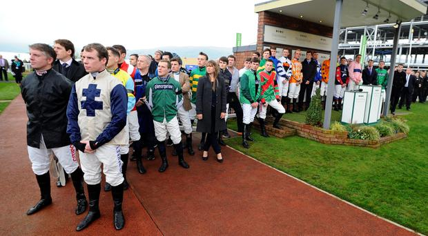 Sombre mood: jockeys during silence at Cheltenham