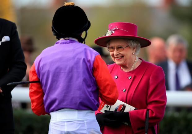 Royal appointment: The Queen with jockey Ryan Moore during the Dubai Duty Free Spring Trials Meeting at Newbury
