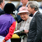 Relaxed: The Queen talks to jockey Ryan Moore and her racing manager John Warren yesterday at Newbury where there was a security alert