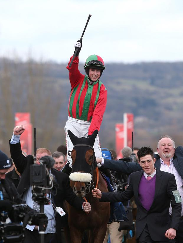 Jockey Bryan Cooper celebrates winning the Jewson Novices' Chase on Benefficient during St Patrick's Thursday at the 2013 Cheltenham Festival at Cheltenham Racecourse, Gloucestershire