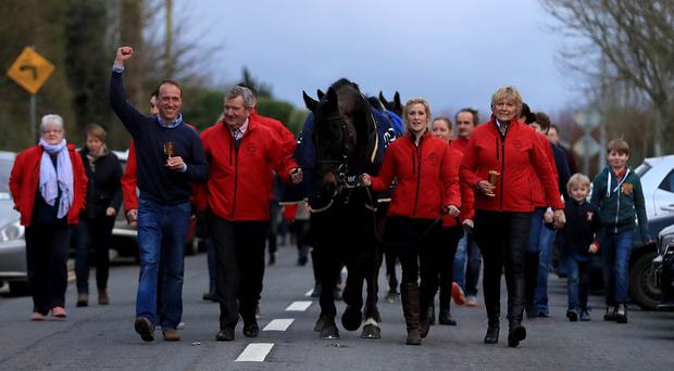 Homecoming hero: Sizing John is led into Moone Village with jockey Robbie Power, head lad Eamonn Leigh, groom Ashley Hussey and trainer Jessica Harrington