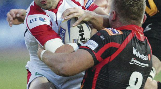 Held up: Ulster's Paul Marshall is tackled by Lewis Evans of the Dragons last night