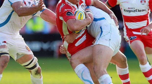 Gloucester's Billy Twelvetrees is tackled by Exeter's Ian Whitten and Ben White during the Aviva Premiership match at Kingsholm.