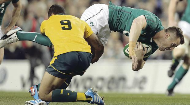 Held up: Tommy Bowe feels the force of a tackle from Australia's Will Genia