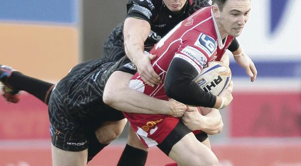 Held up: Kristian Phillips of Scarlets is tackled by Ben John and Sam Lewis of Ospreys during yesterday's match