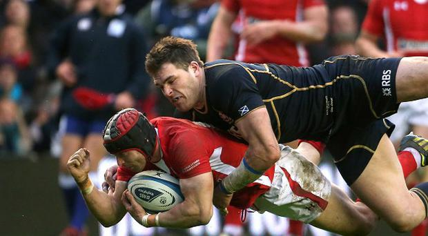 Wales' Leigh Halfpenny is tackled by Scotland's Sean Lamont (top) during the RBS Six Nations match at Murrayfield Stadium, Edinburgh in 2013