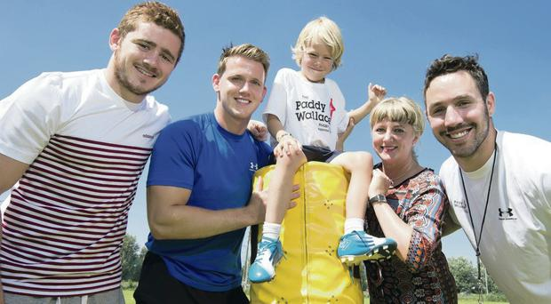Master class: Paddy Wallace (right) and Ulster stars Paddy Jackson and Craig Gilroy pass on a few tips to young Jack Ham at his Tesco-supported coaching camps, Included is Tesco's Caoimhe Mannion